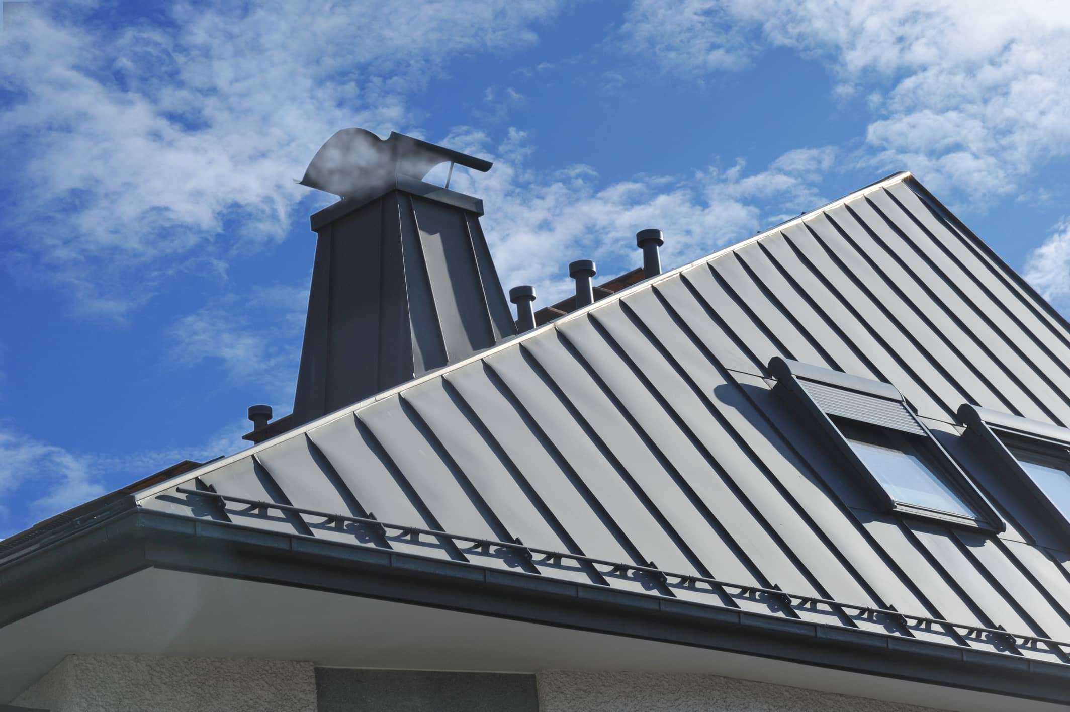 This is an image of a residential roofing with metal roofing and sun roof.