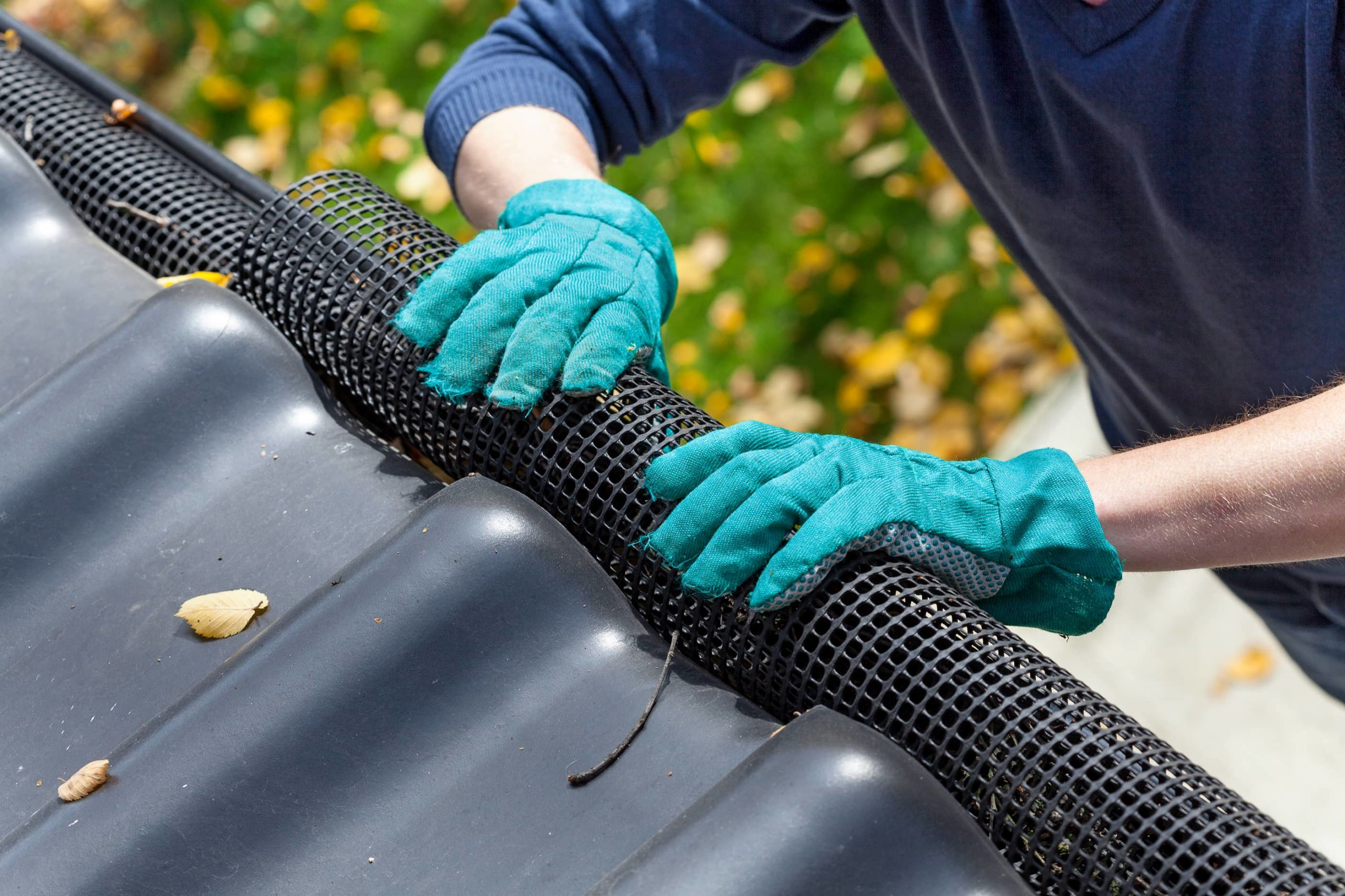 This is an image of a roofing contractor installing a gutter guard to prevent debris clogging.