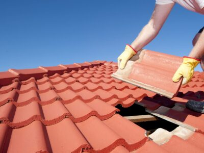 This is an image of a contractor repairing a roofing and replacing a roof shingle.