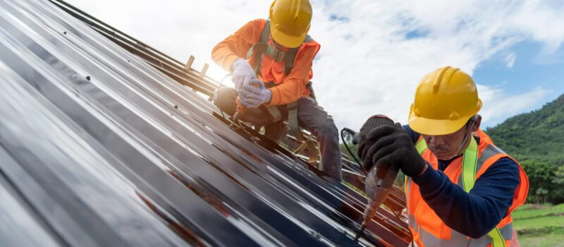 This is an image of two roofing contractors installing a metal roofing.